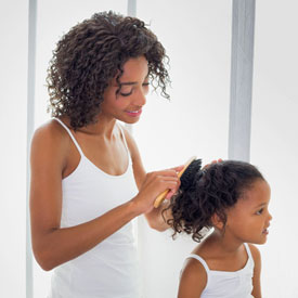 mom brushing daughters hair before head lice treatment